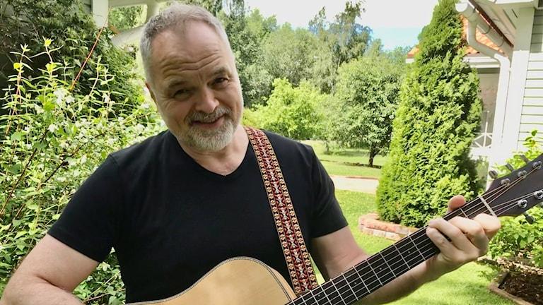 Charles Plogman soittaa kitaraa ja katsoo kameraan.
