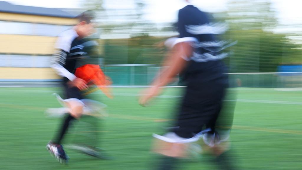 Två unga spelar fotboll i suddig bild