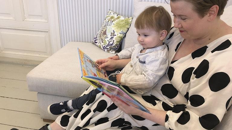 Äiti lukee kirjaa sylissä istuvalle taaperolle.