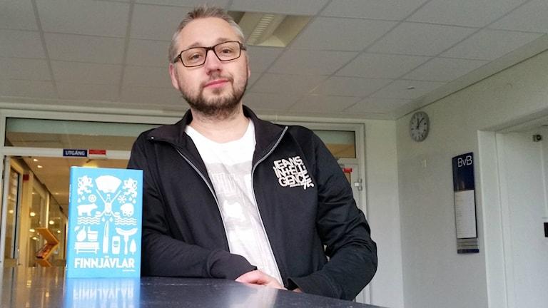 Redaktören för antologin, Kristian Borg, står vid ett bord med boken.