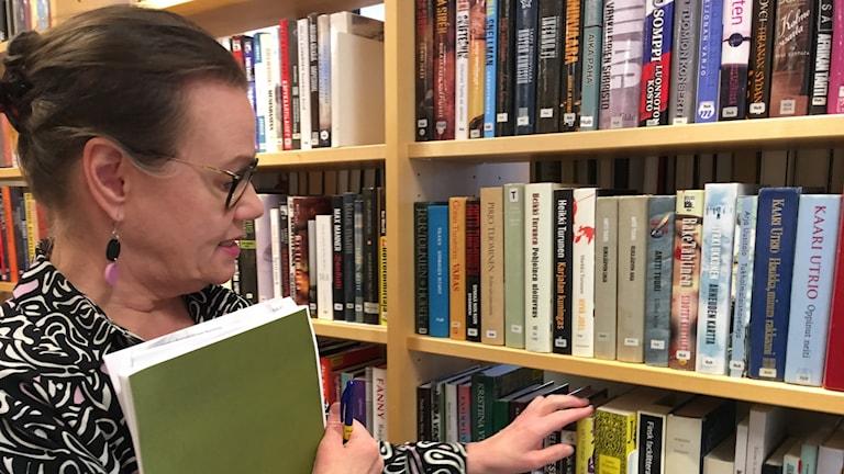 Reetta Stenström pitää vihkoa kädessä ja osoittaa kirjaa hyllyssä, joissa suomenkielisiä teoksia näkyy pitkissä riveissä.