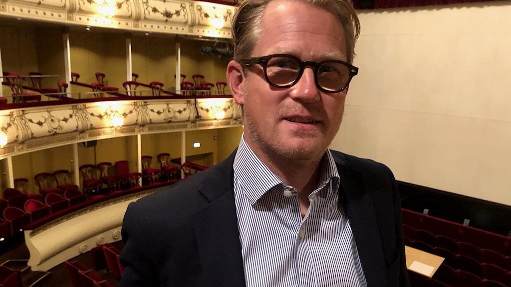 Teatterinjohtaja Joachim Thibblin, taustalla Svenska Teaternin katsomoaitioita.