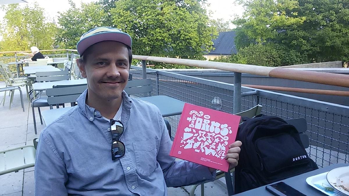 Lippalakkipäinen Anssi Arte istuu terassilla kauluspaita päällä ja pitää käsissää vaalenpunakantista kirjaansa. Kuva: Marcus Floman