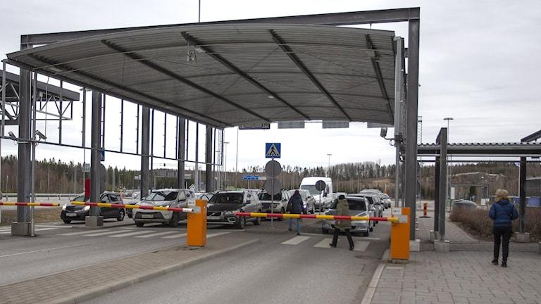 Suomen ja Venäjän välinen raja, puomi, autoja katoksessa. Ihminen kävelee kohti rajaa.