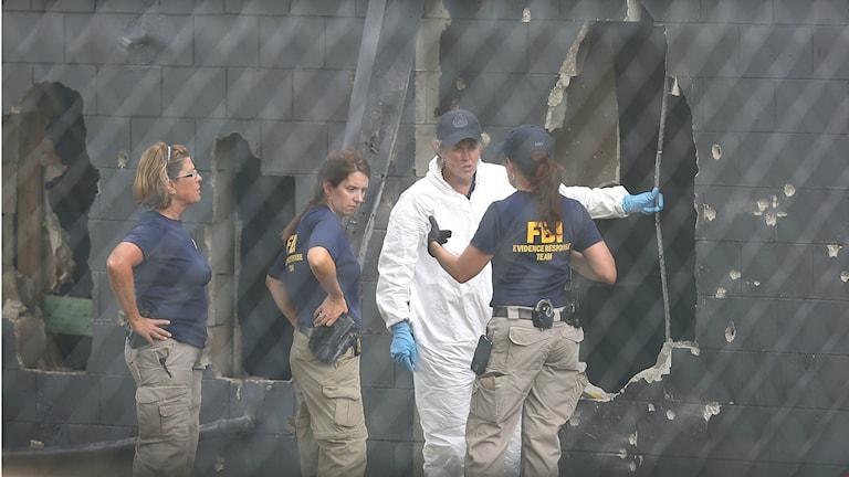 FBI-agentit tutkivat Pulse yökerhon takaseinän vaurioita. Betoniseinässä useita reikiä.