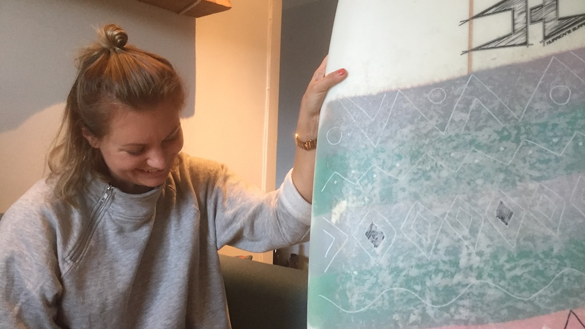 Sandra Johansson katsoo nauraen pystyssä pitämäänsä surffilautaa. Kuva: Timo Laine/SR Sisuradio