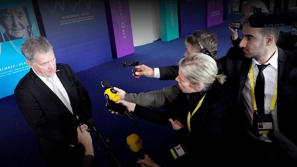 Mies vasemalla haastatellaan. Oikealla usea ihminen jolla on mikrofonit kädessä.
