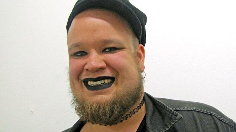 Naurava, parrakas henkilö lähikuvassa, mustaa huulipunaa, musta lätsä, musta farkkutakki, tatuointi kaulan ympärillä, korvarengas.
