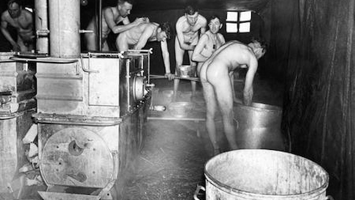 Historiallinen kuva: miehiä armeijan saunassa.
