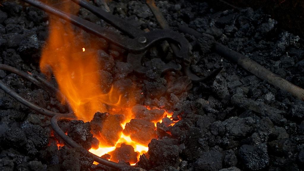 Rautakankia mustilla hiilillä liekin roihutessa vasemmalla.