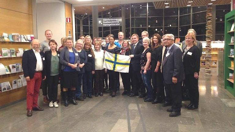 Kuvassa näkyy Haningessa kokoontuneet poliitikot hallintoalueista. Keskellä seisoo demokratiaministeri Alice Bah Kuhnke ja pitää ruotsinsuomalaista lippua.