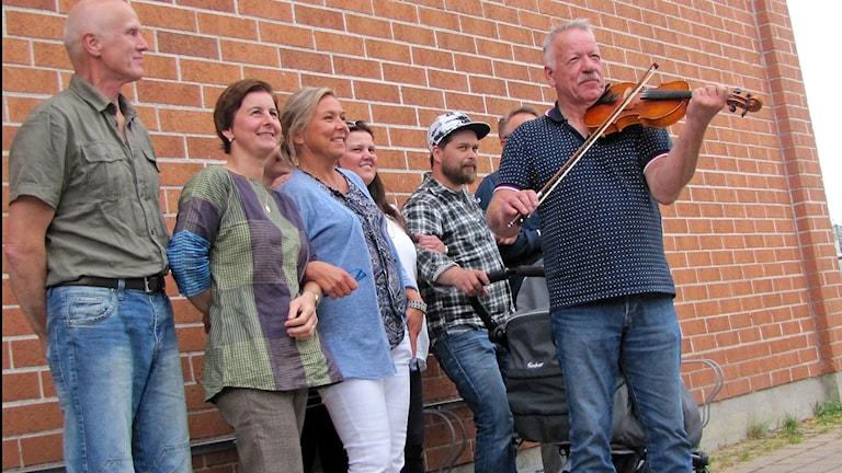 Seitsemän ihmistä seisoo tiiliseinän edessä. Yksi mies soittaa viulua.