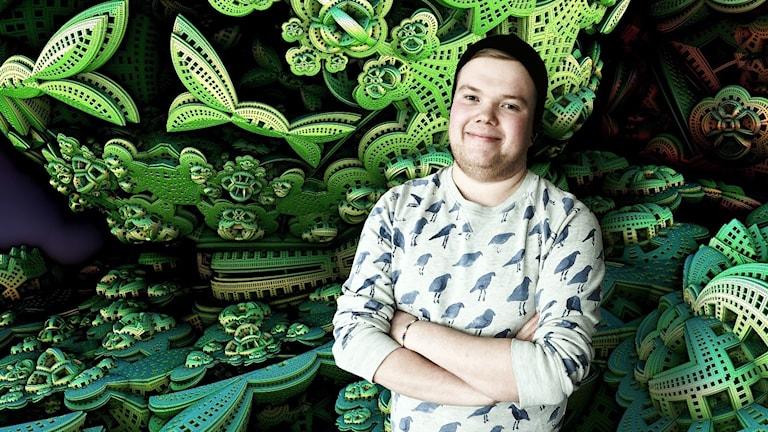 Tuomas Laulajainen står med armarna i kors framför färgglad vägg.