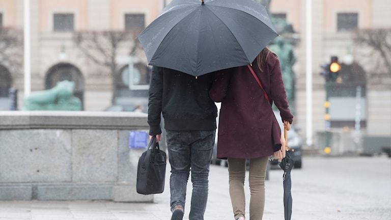 Kuvassa nainen ja mies kävelevät saman sateenvarjon alla.