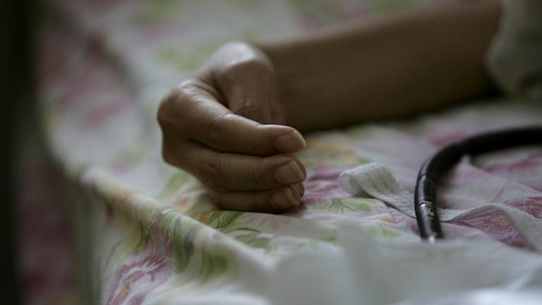 Kuvassa on sängyllä, kukikkaan lakanan päällä lepäävä käsi. Kuva: Fredrik Sandberg / TT