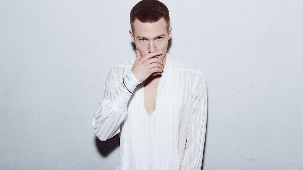 Olavi Uusivirta valkoisessa paidassa käsi suun edessä. Kuva: Tero Ahonen/Hög Music