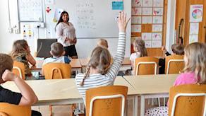 Kuvassa luokka huone jossa oppilaita ja opettaja, yksi oppilas viittaa.