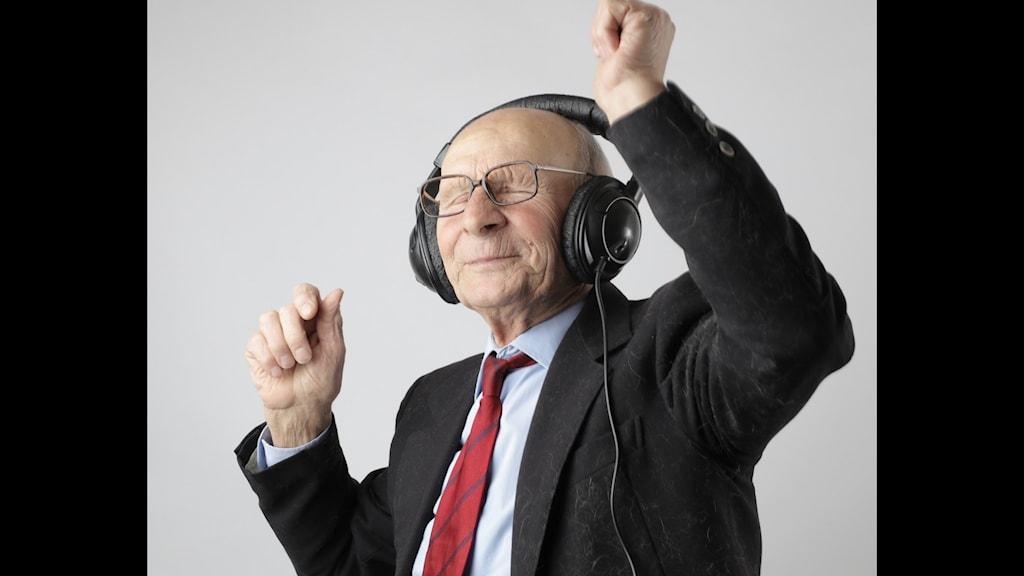 Leende äldre man dansar med hörlurar på öronen.