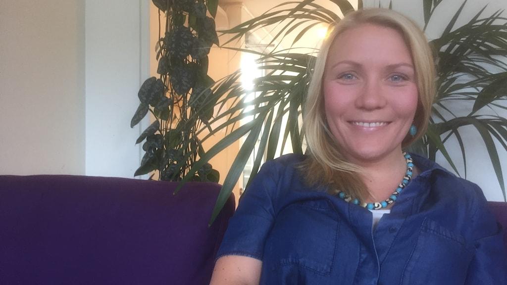 Vaaletukkainen Liselott Lindström istuu sohvalla sinisessä paidassa ja hymyilee. Kuva: Timo Laine/SR Sisuradio