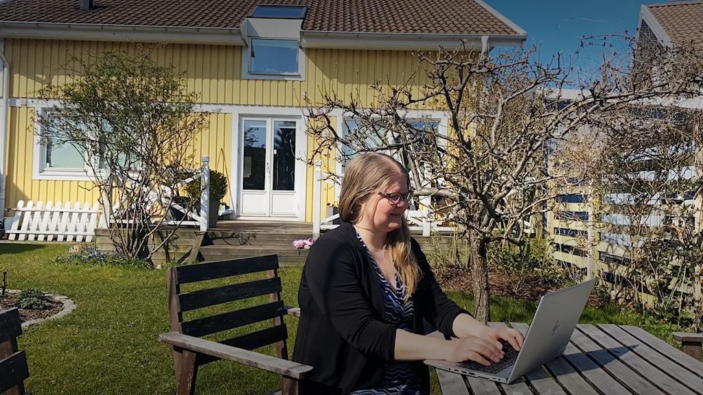 Sanna Jälevik istuu puutarhassa keltaisen huvilan edessä ja hän katsoo tietokoneeseensa.