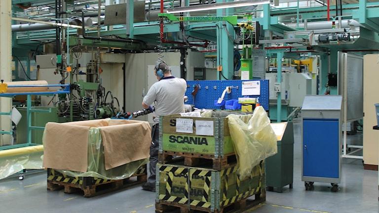 Scanian kuorma-autotehtaan sisällä otettu kuva. Mies työskentelee.