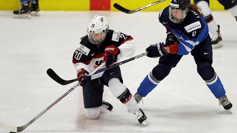 Två kvinnliga ishockeyspelare mitt i matchen