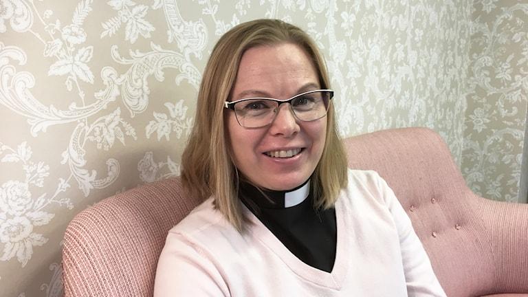 Hymyilevä Johanna Suban istuu vaaleanpunaisella sohvalla, hänellä on yllään papinpaita.