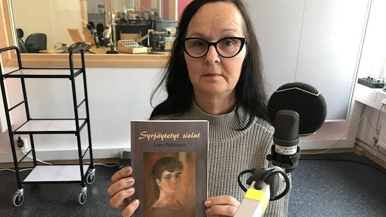 Anne Pehkonen kädessään Syrjäytetyt sielut -kirja.