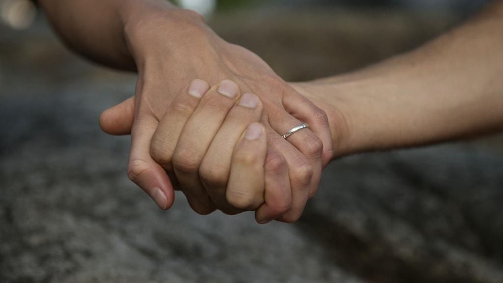 Bild på ett par händer som håller i varandra.