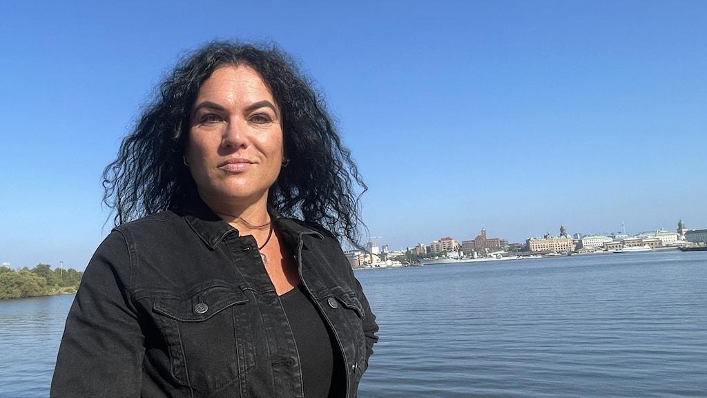 nainen, jonka taustalla joki ja häämöttävä kaupunki.