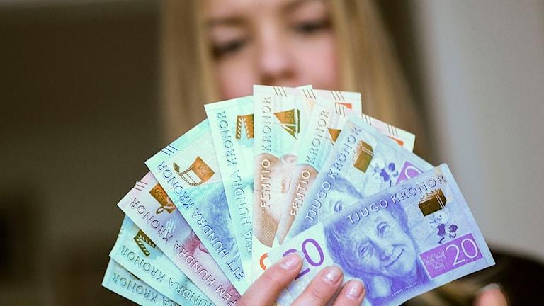 Nainen tukku seteleitä kädessään