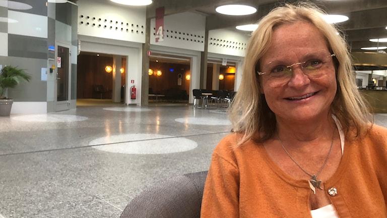 Nauravainen, silmälasipäinen ja vaaleatukkainen Tarja Brandeus istuu Radiotalon aulassa oranssissa neuleessa ja katsoo kameraan. Kuva: Timo Laine/SR Sisuradio.