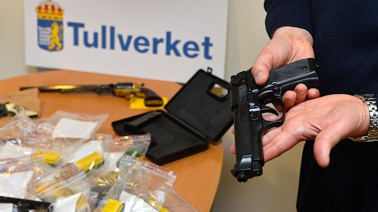 Kuvassa ampuma-ase tullivirkailijan kädessä, taustalla pöytä joka täynnä takavarikoituja aseita.
