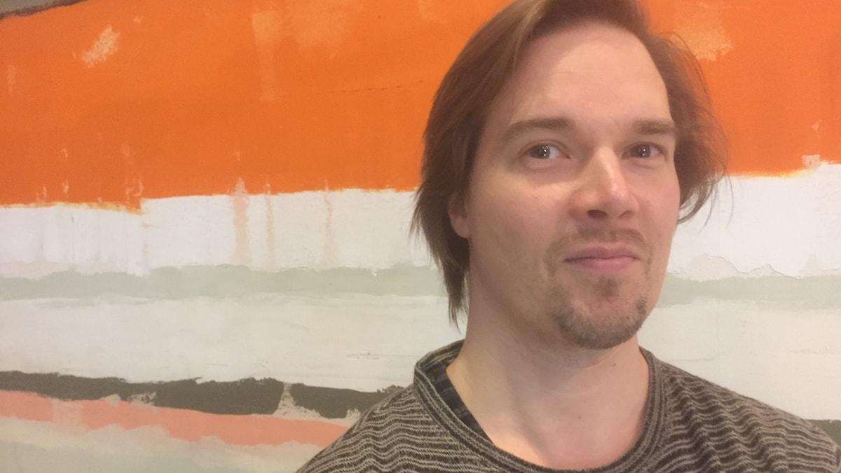 Raitapaitainen Tatu Metsätähti katsoo kameraan värikkään seinän edessä. Kuva: Timo Laine/SR Sisuradio.