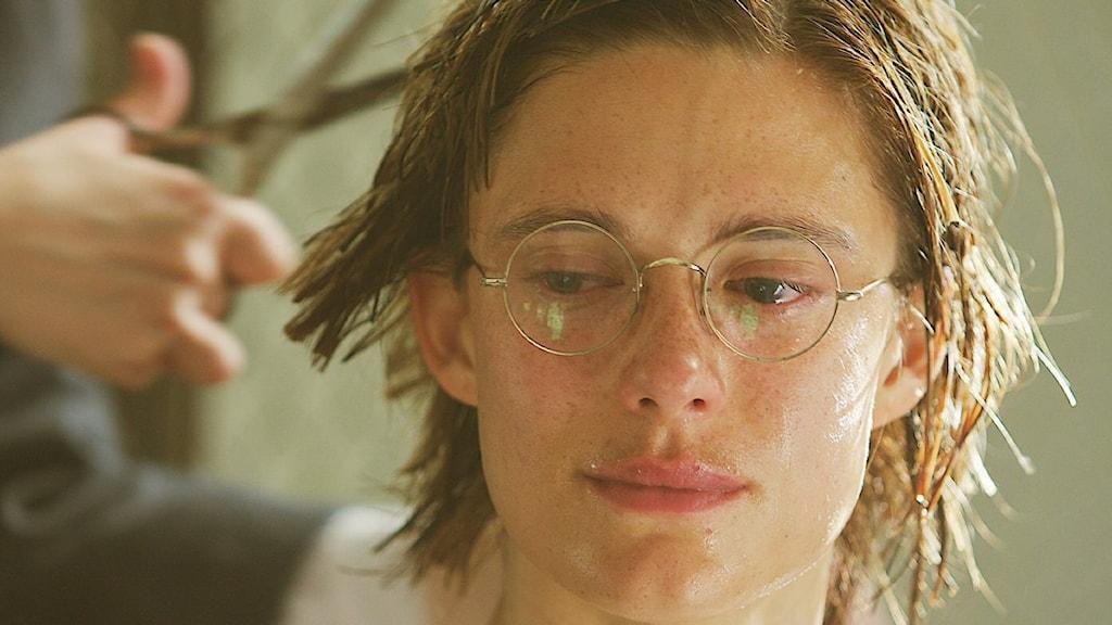 Kvinna med glasögon får sitt hår klippt av en annan person.