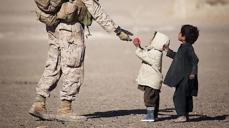 En soldat ger två barn en röd boll