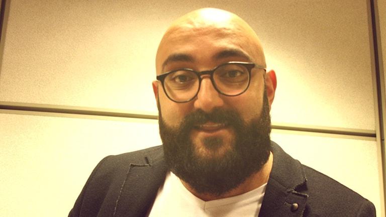 Koomikko Ali Jahangirin kasvokuva mustilla pyöreillä silmälaseilla.