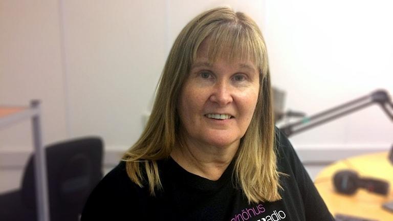En kvinna med svart t-shirt och medlblont hår sitter i en radiostudio.