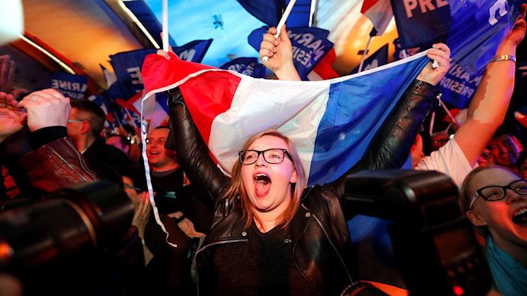 En kvinna med Frankrikes flagga och glasögon jublar.