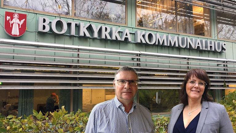 Lars Johansson och Ebba Östlin och texten Botkyrka kommunalhus på ett hus.
