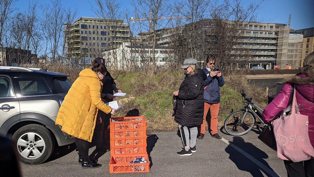 Malmössä museon parkkipaikalla joukko ihmisiä odottaa leipätilaustaan, kun Suomi yhdistys jakaa leipää.