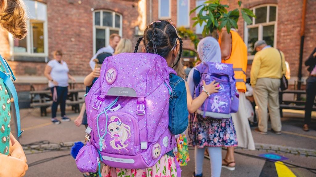 lapsia ja aikuisia koulun sisäpihalla