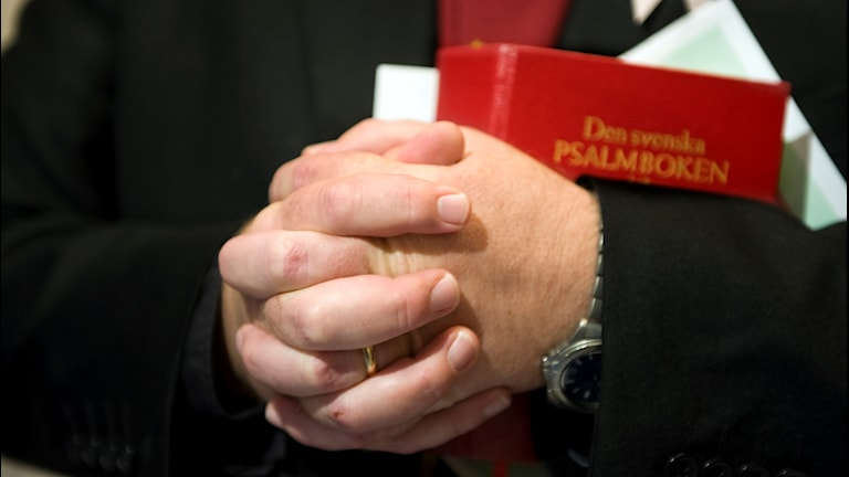 Präst men knäppta händer och en röd psalmbok