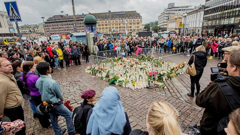 Kuvassa näkyy ihmisiä Turun kauppatorilla, he ovat kokontuneet kynttilä- ja kukkameren ympärille.