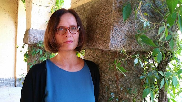 Susanna Alakoski nojaa graniittiseen pylvääseen, jota kietää villiviini. Alakoskella on päällä sininen pusero, musta neuletakki.