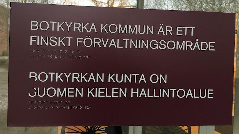 """Kunnantalon kyltti, jossa lukee """"Botkyrkan kunta on suomen kielen hallintoalue"""" ruotsiksi ja suomeksi."""