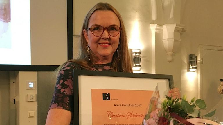 Kuvassa hymyileva carina Söderström sylissään kunniakirja ja kukkasia.