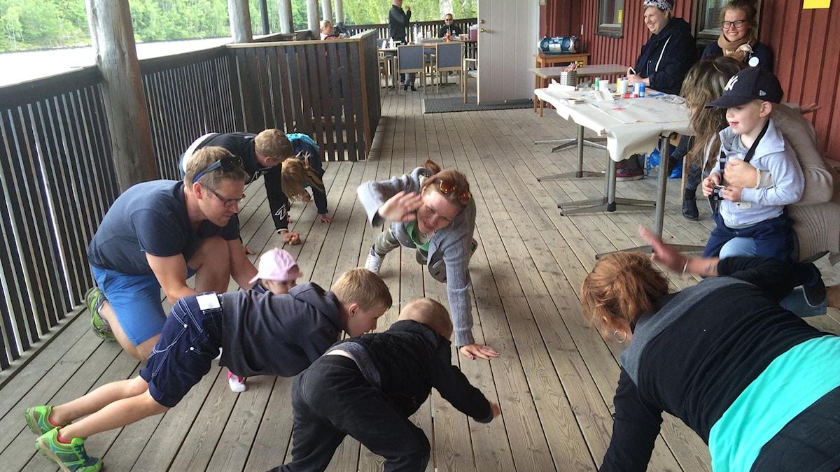 Terassijumppaa Fin i Väst- perhepäivän aikana, lapset ja aikuiset ryömivät ulkoterassilla