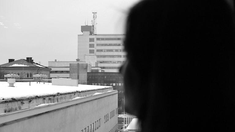 En kvinna tittar ut på fönstret