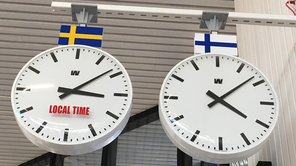 Kaksi kelloa katossa. Toinen näyttää Ruotsin ja toinen Suomen aikaa.